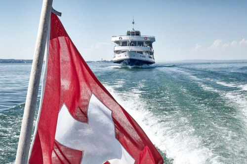 The Swiss flag, behind it the MS St. Gallen